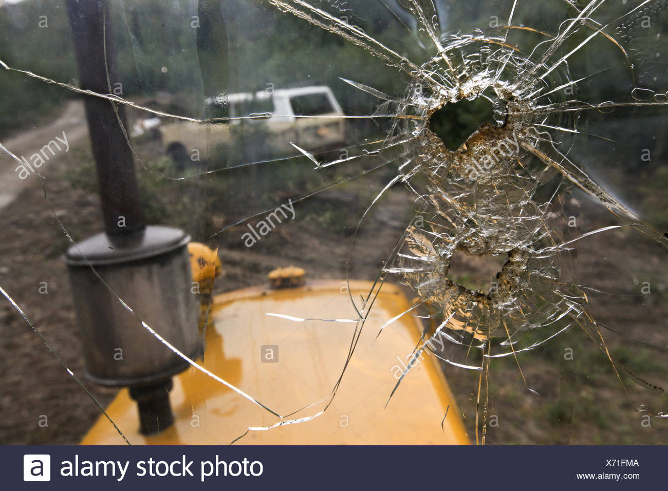Bullet holes are visible in the windshield of construction equipment that sits in Denali National Park and Preserve. - Stock Image