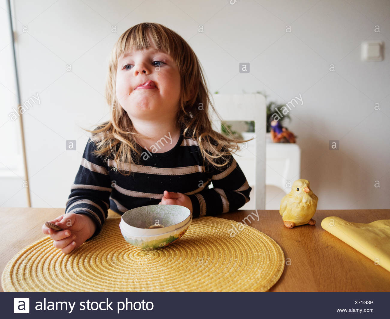Little girl sticking out tongue at dining table - Stock Image