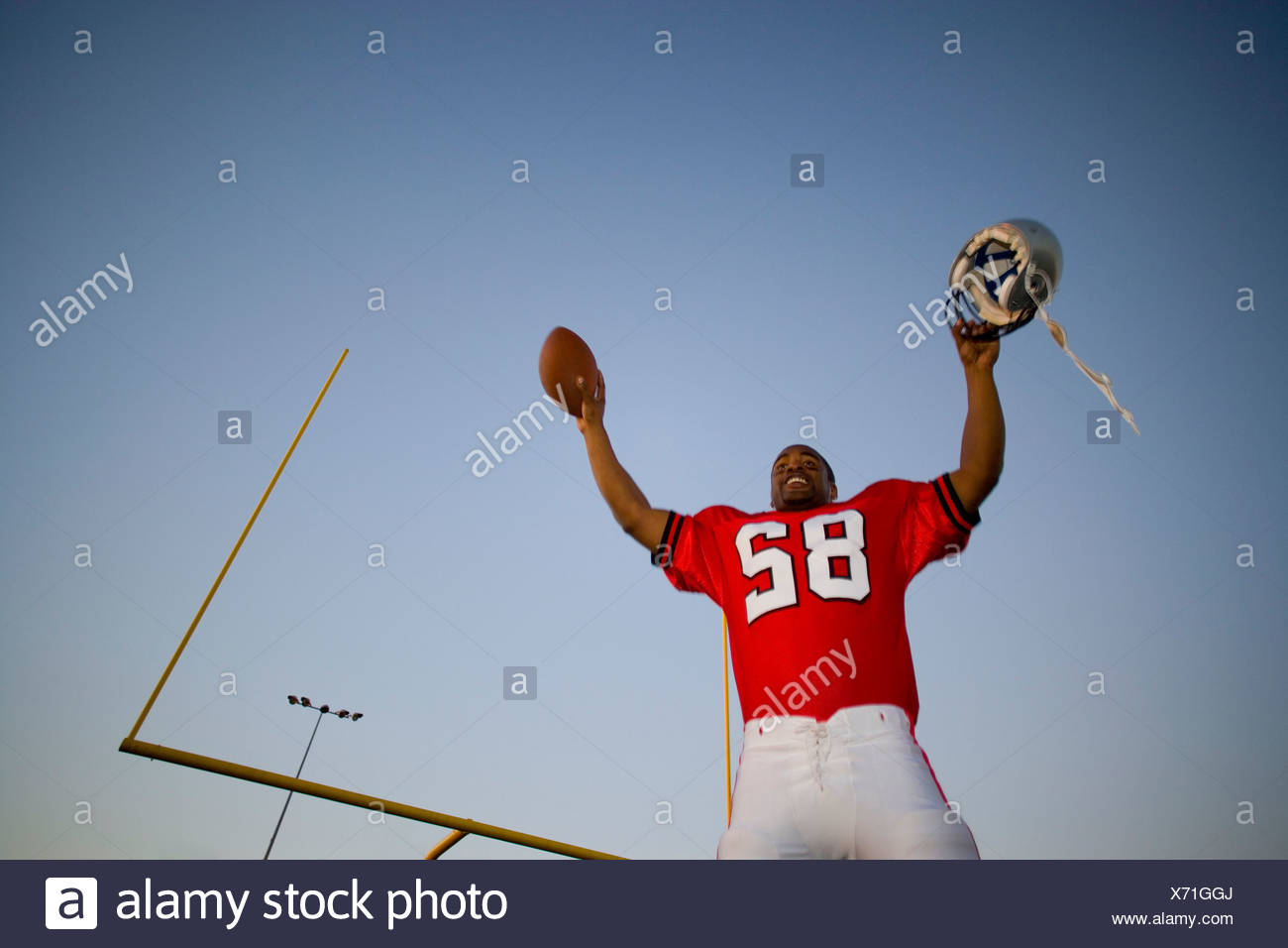 American football player, in red strip, celebrating victory on pitch at sunset, arms up, holding ball and protective helmet - Stock Image