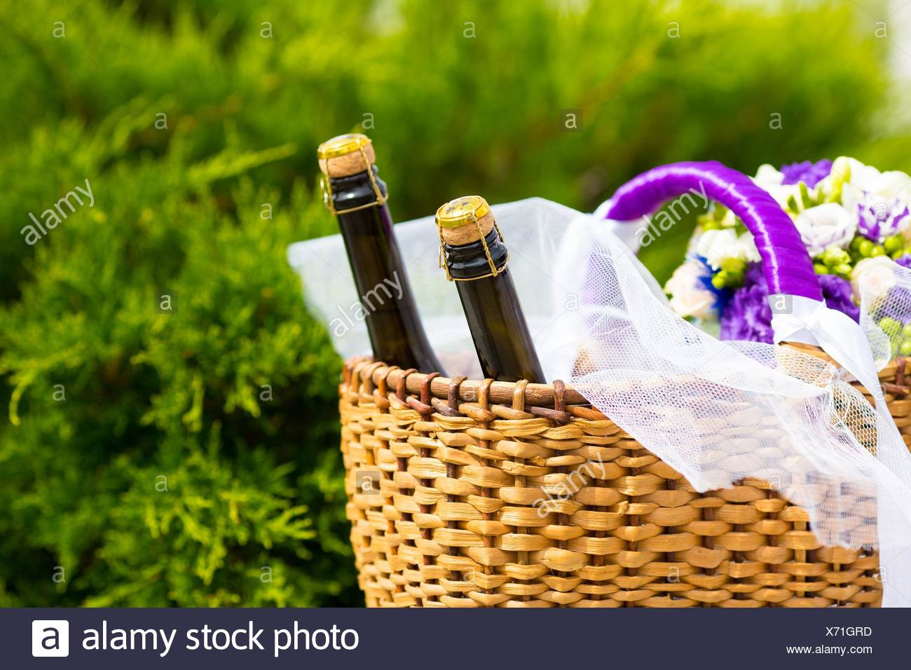 Wicker basket with two bottles champaign and flowers. - Stock Image
