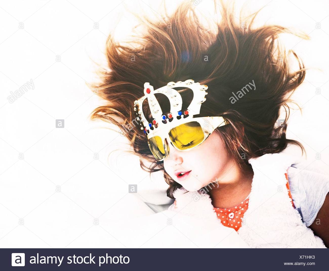 Cute Girl Wearing Decorative Glasses While Sleeping On Bed - Stock Image