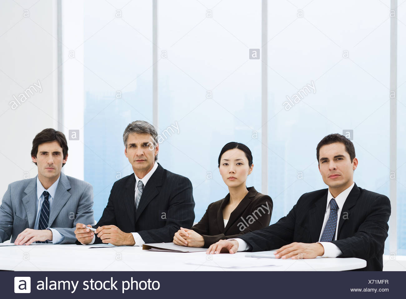 Business associates sitting at table, looking at camera, serious expressions - Stock Image