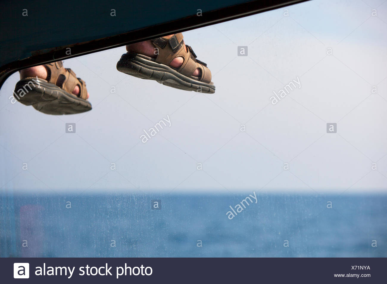 Thailand, Phuket, Thaimaa, Feet of person sitting on roof of vehicle - Stock Image