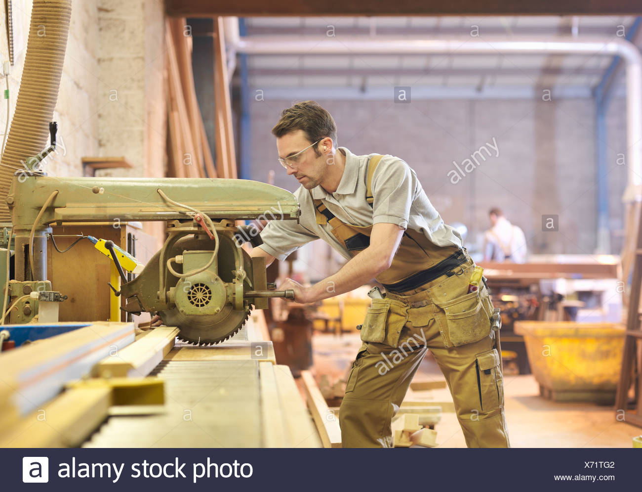 Woodworker sawing timber - Stock Image