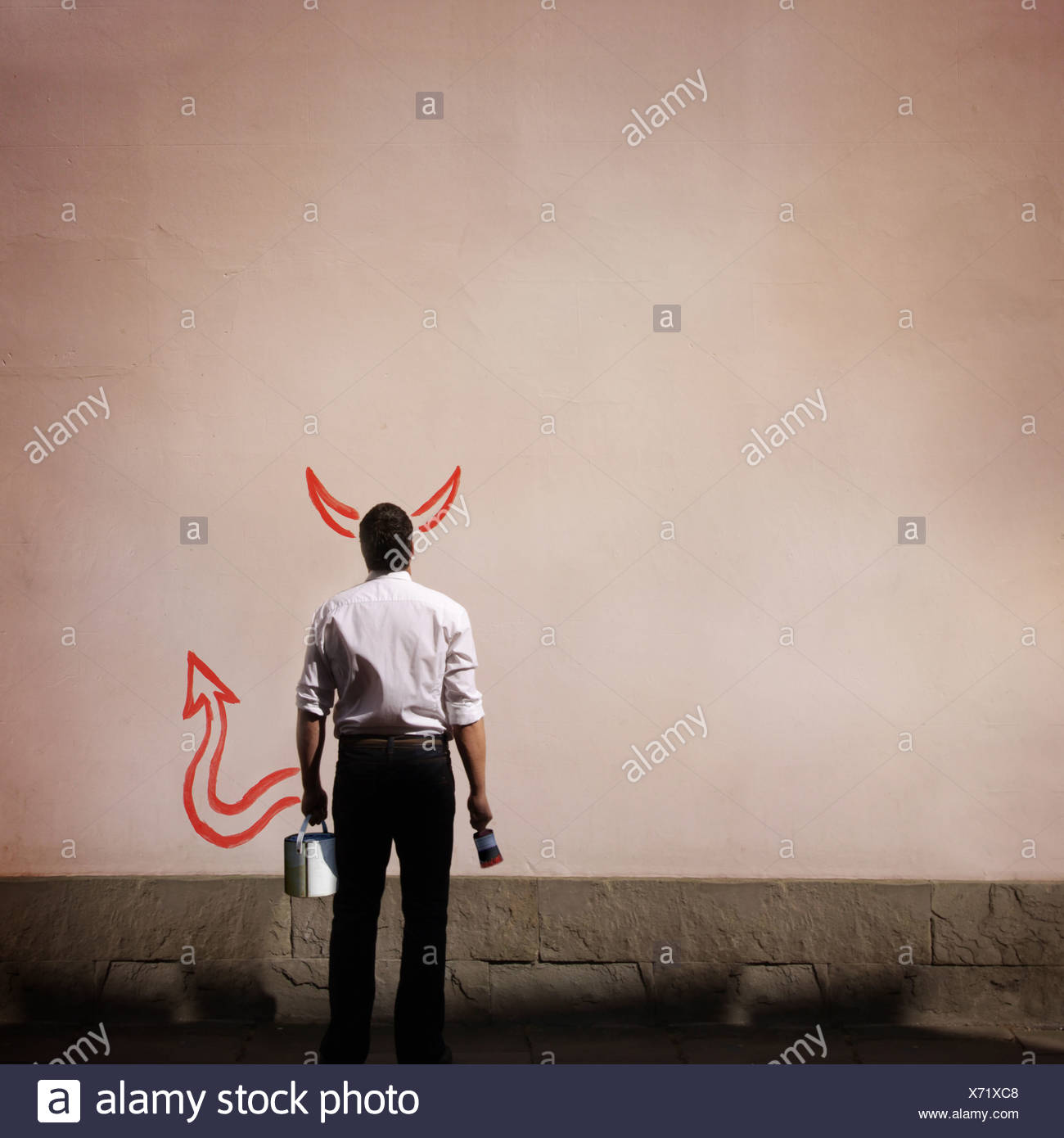 man with devil horns and tail painted on wall - Stock Image