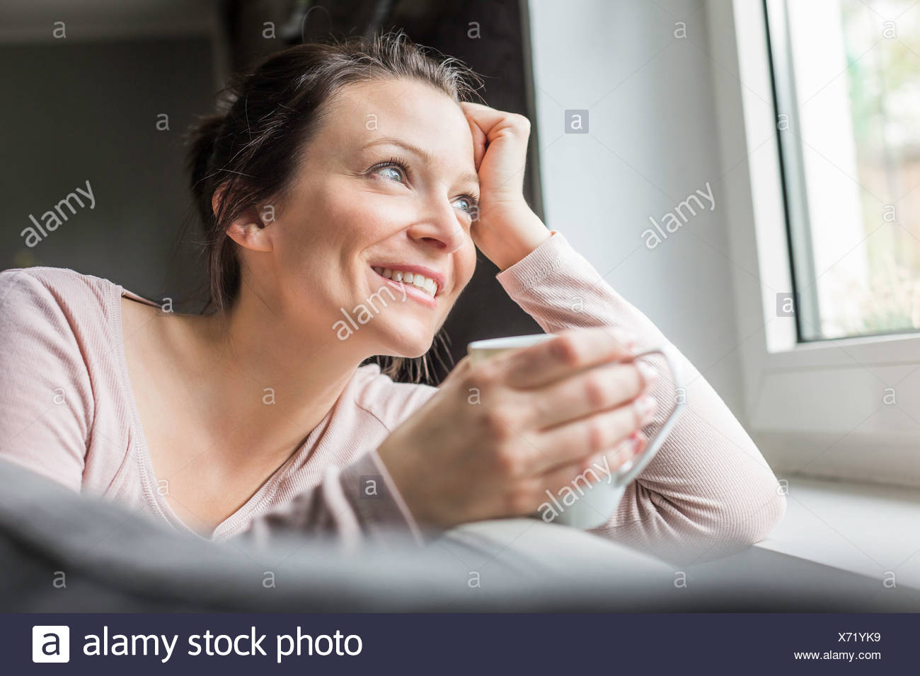Mid adult woman looking out of window with coffee - Stock Image