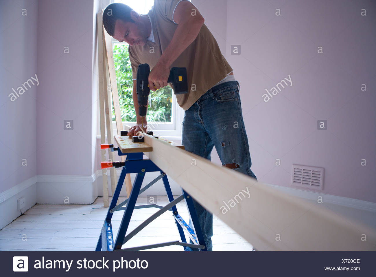 Man using electric drill on beam - Stock Image