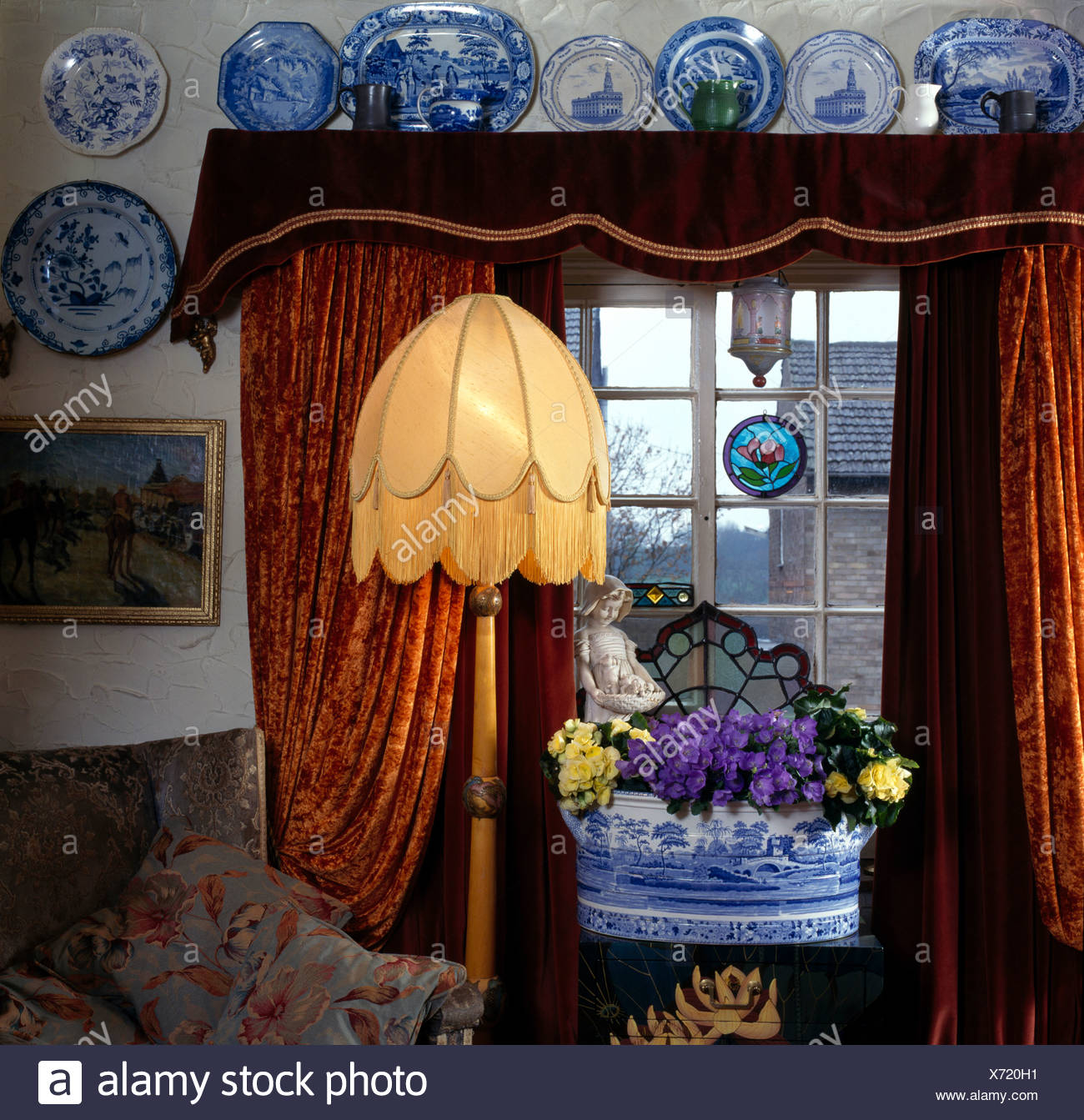 Blue White China On Wall Above Window With Red Brown Velvet Curtains In Cottage Living Room With Lighted Thirties Floor Lamp Stock Photo Alamy