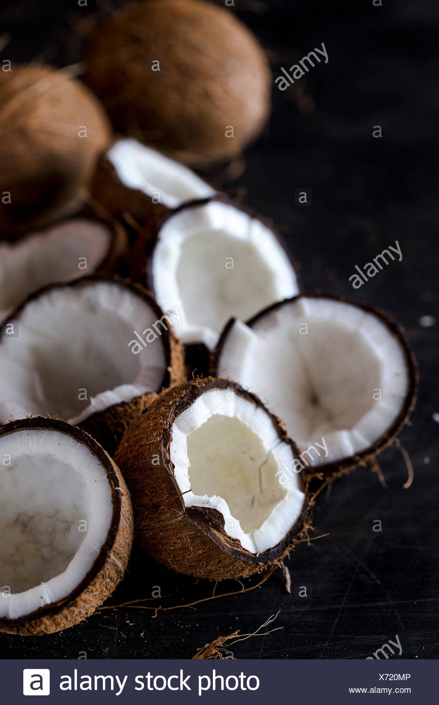 Fresh cracked coconuts are displayed on a dark background - Stock Image