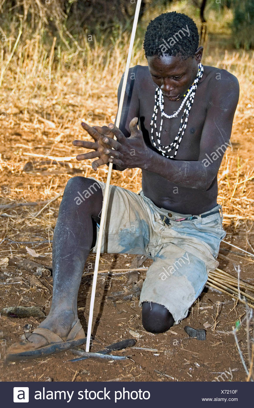 Hadzabe bushman making up fire with a stick, Tanzania - Stock Image