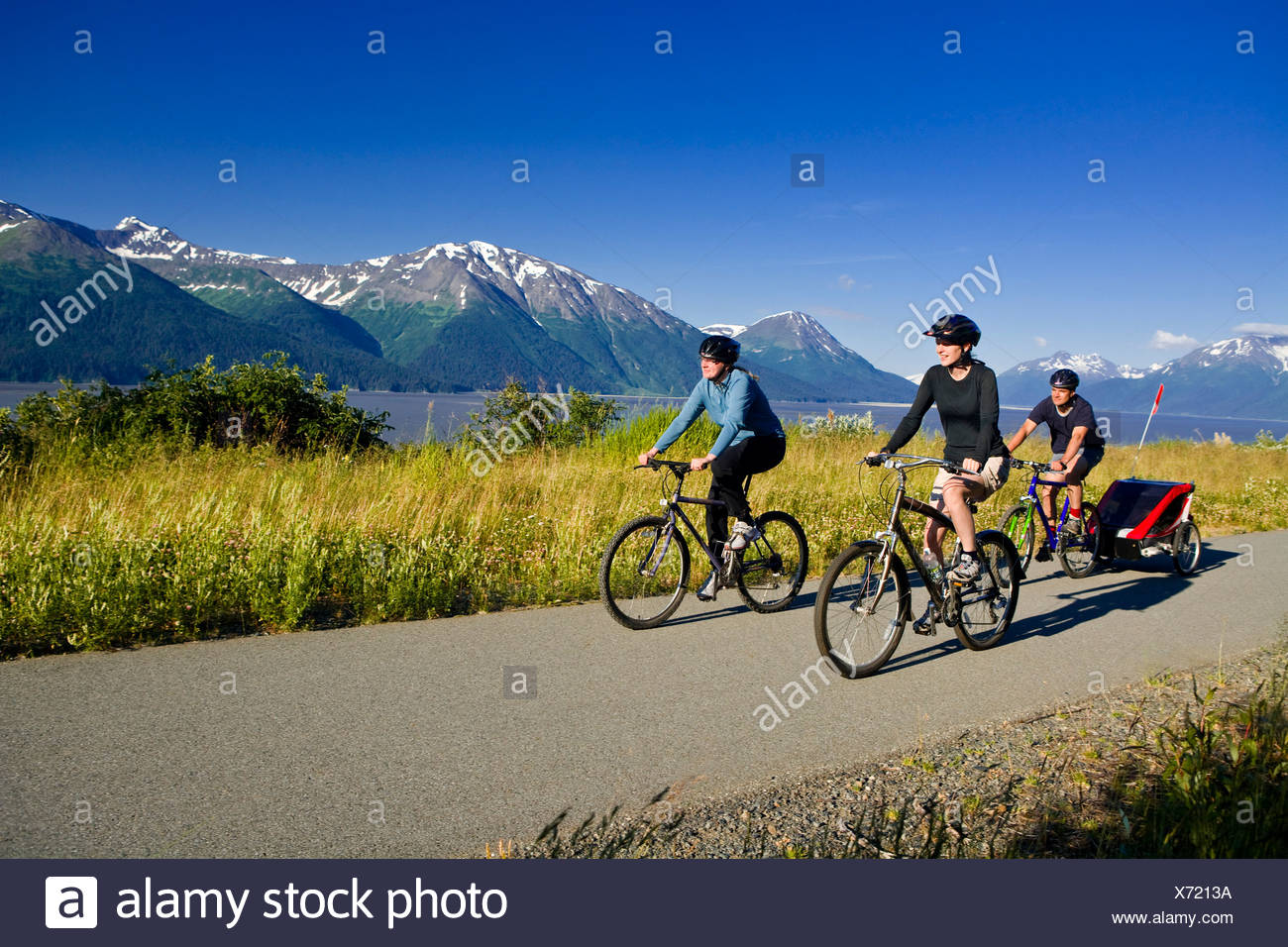 Group of bikers with baby in storller on the Bird Point to Girdwood bike trail along Turnagain Arm, Southcentral Alaska Summer - Stock Image