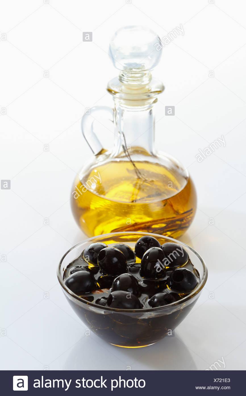 Black Olives In Glass Bowl And Bottle Of Olive Oil On White