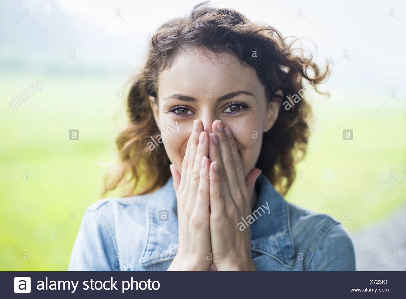A young woman in a rural landscape with windblown curly hair. Covering her face with her hands and laughing. - Stock Image