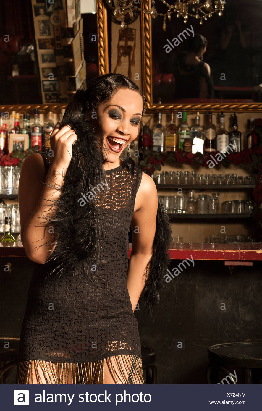 Young female Afro-American styled in the way of roaring Twenties in a bar - Stock Image