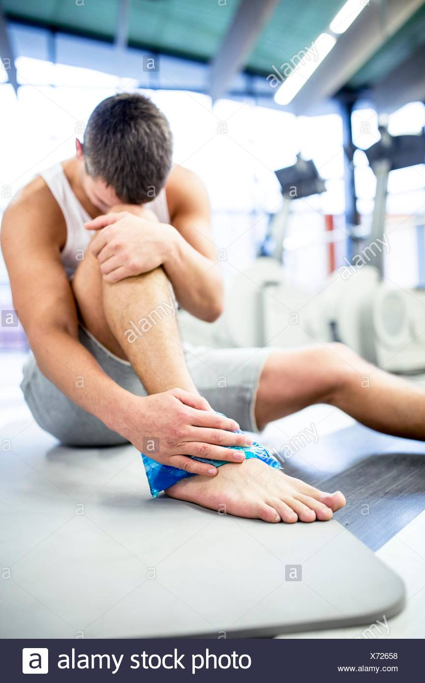 PROPERTY RELEASED. MODEL RELEASED. Young man holding ice pack on injured ankle in gym. - Stock Image