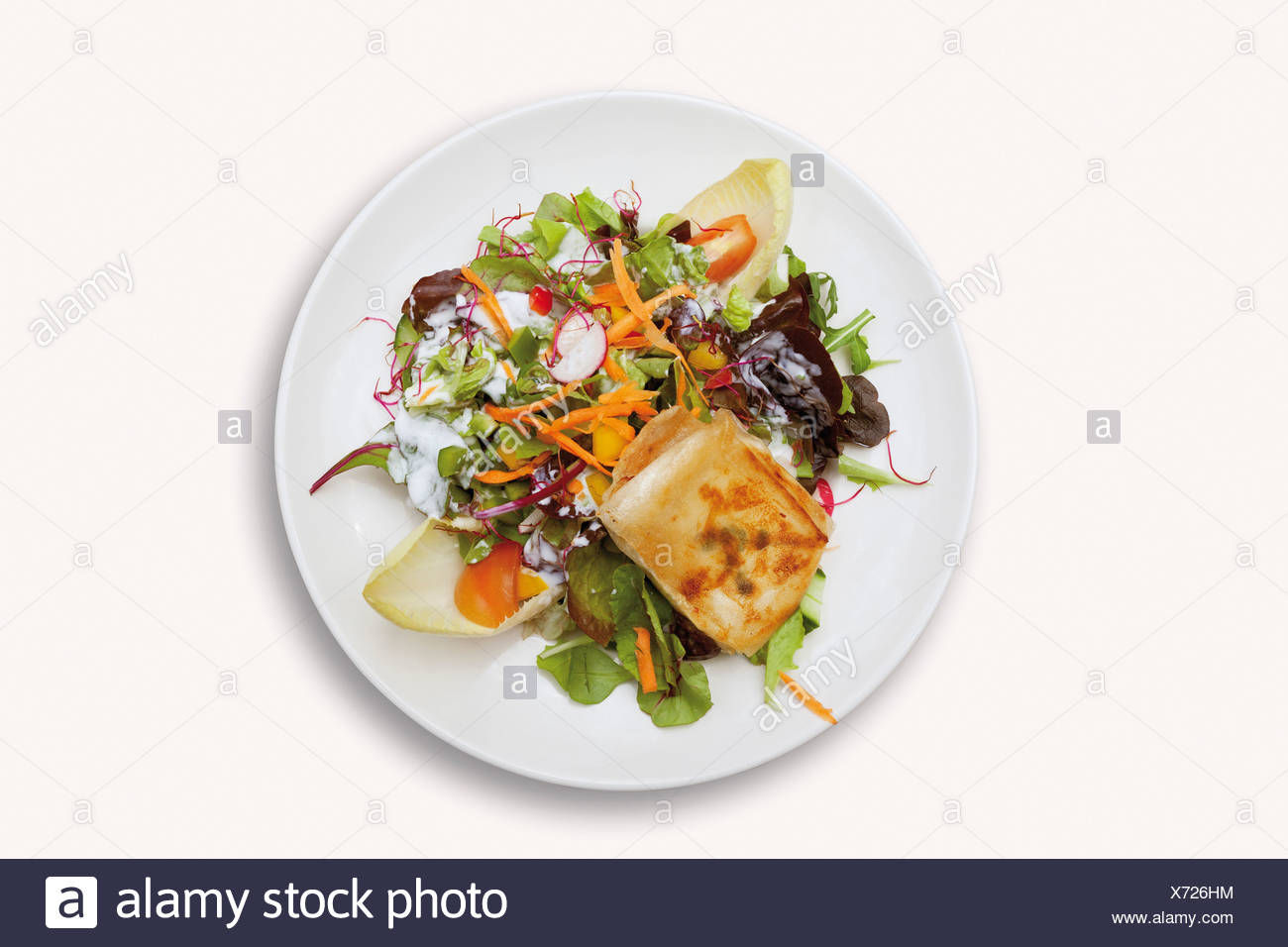 Close up of goat cheese au gratin with mixed salad on white background - Stock Image