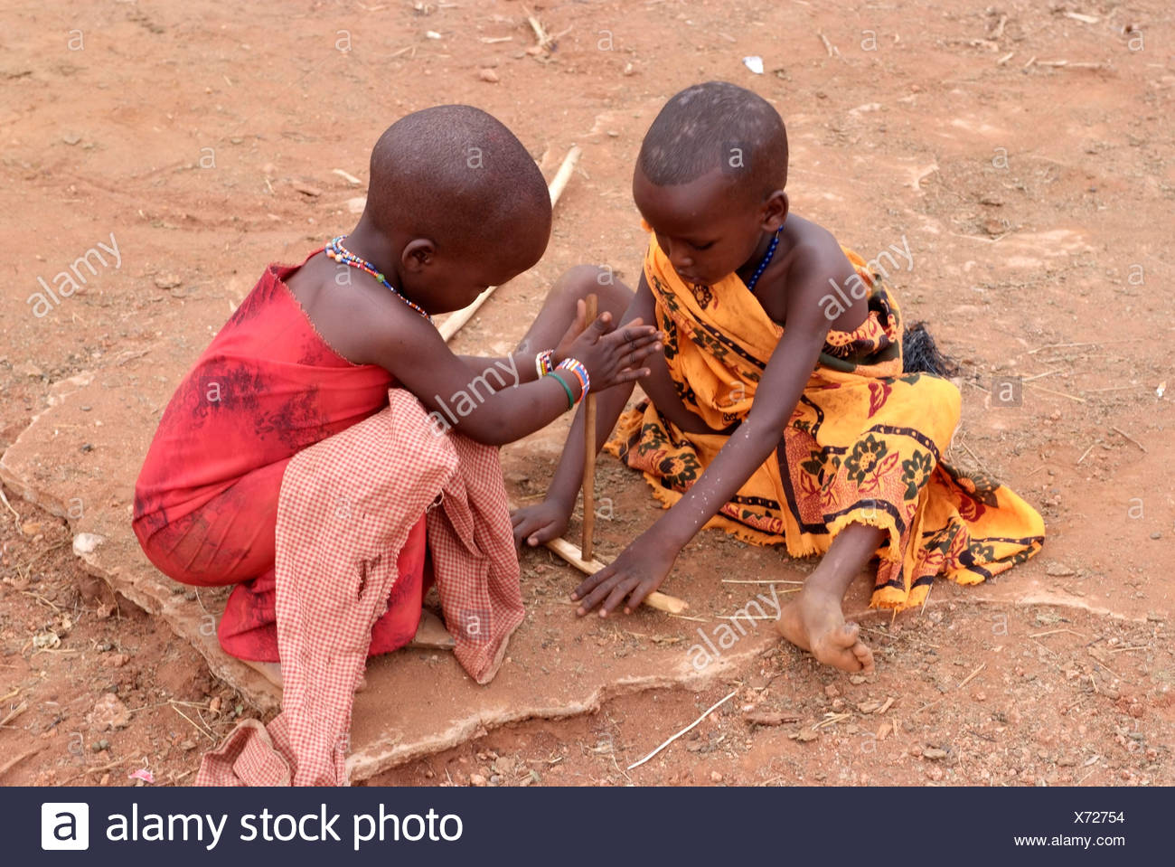 Massai children are pretending to ignite a fire, Kenya, Africa - Stock Image