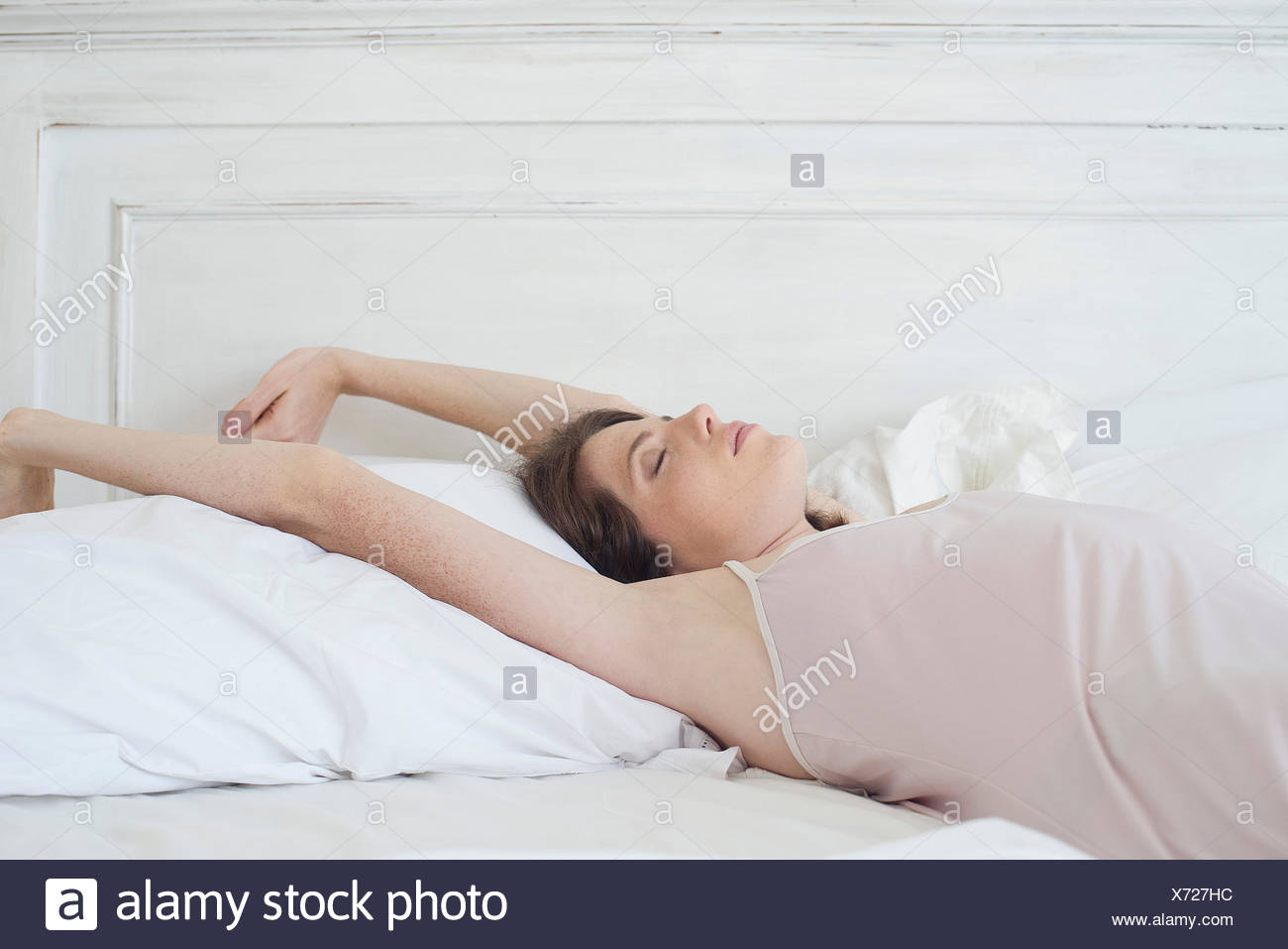 Woman lying on back in bed stretching - Stock Image