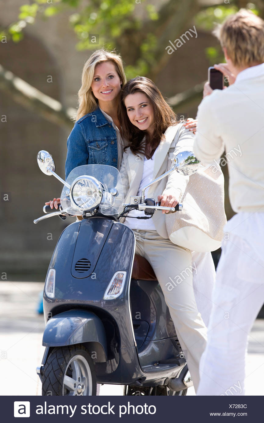 Man taking pictures two young women on scooter outdoors, Stuttgart, Baden-Wurttemberg, Germany - Stock Image
