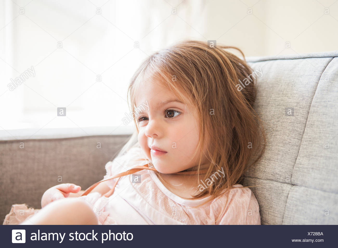 Toddler girl making a face on sofa - Stock Image