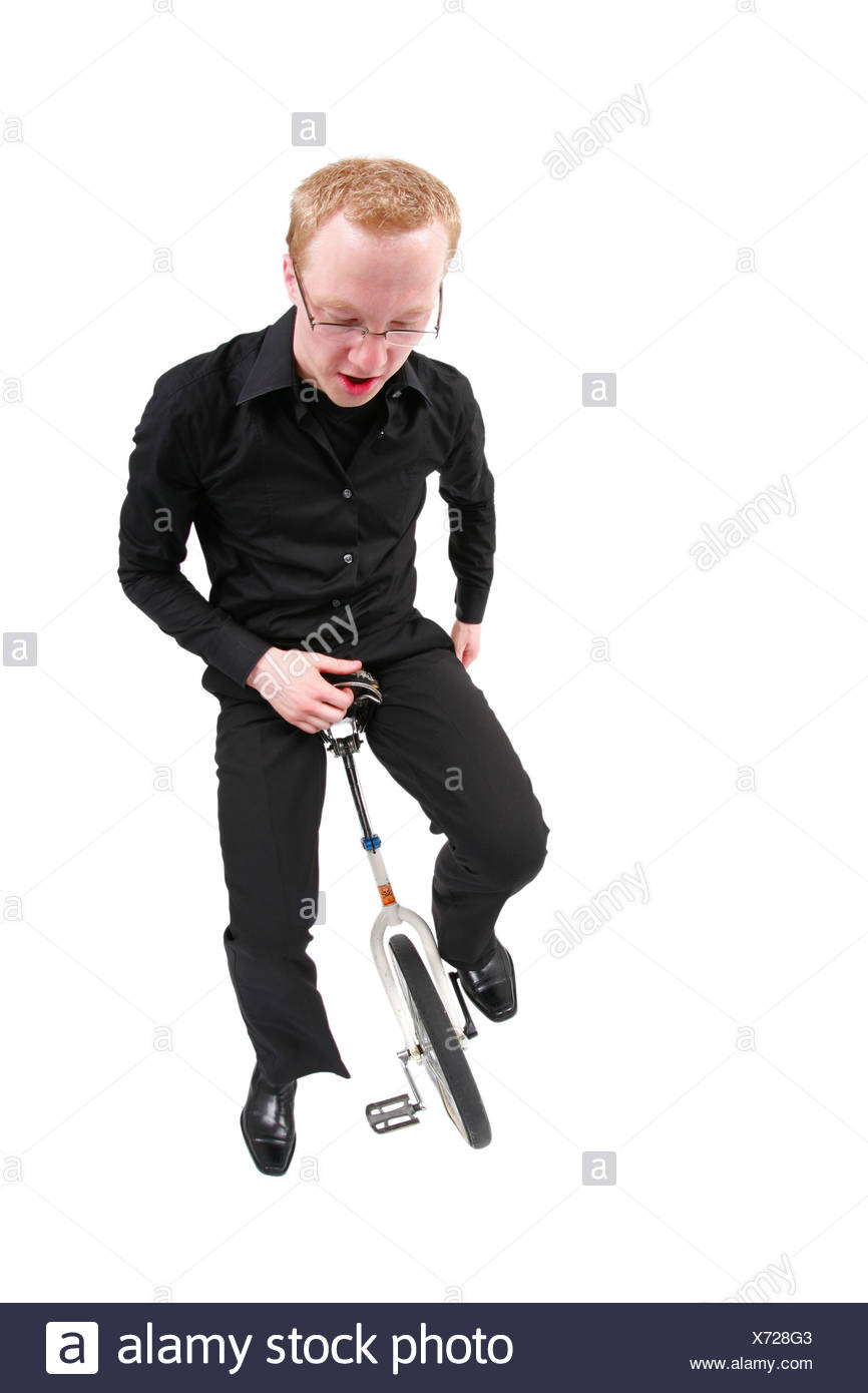 young man riding unicycle - Stock Image