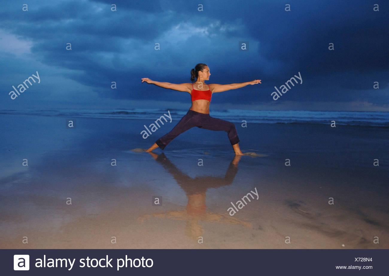 Female performs yoga on beach - Stock Image