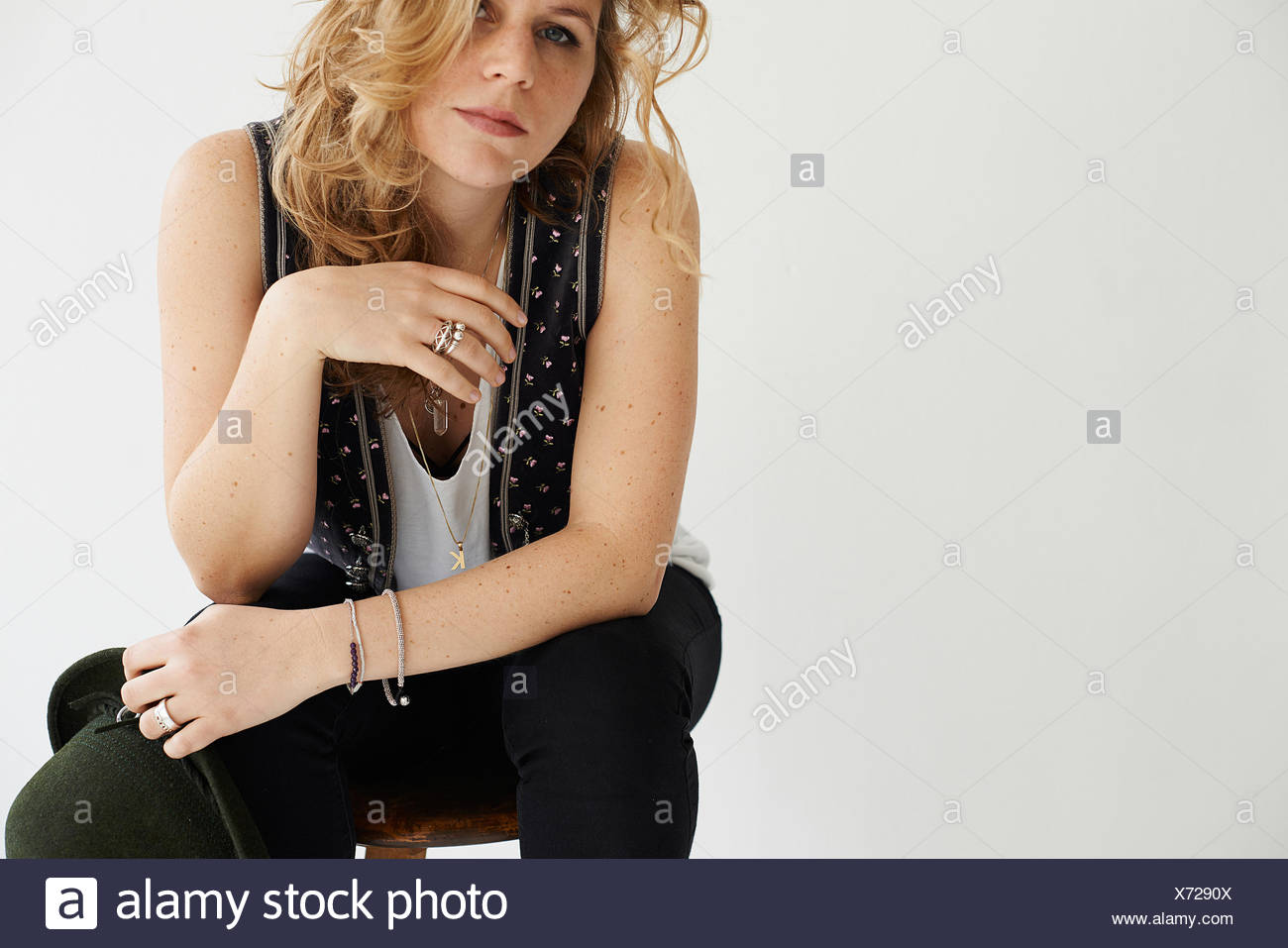 Mid adult woman sitting resting elbow on knee - Stock Image