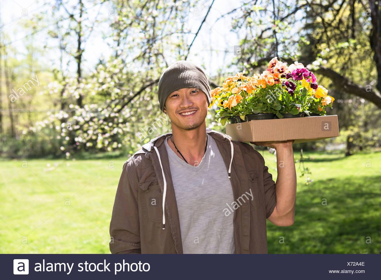 Man holding box of flowers - Stock Image