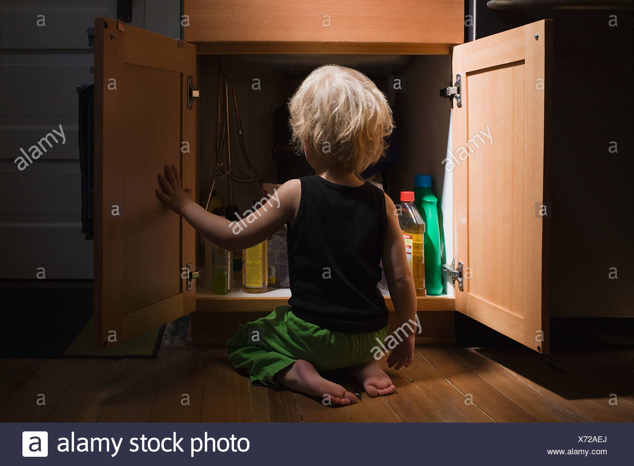 Little boy opening cupboard of cleaning products - Stock Image
