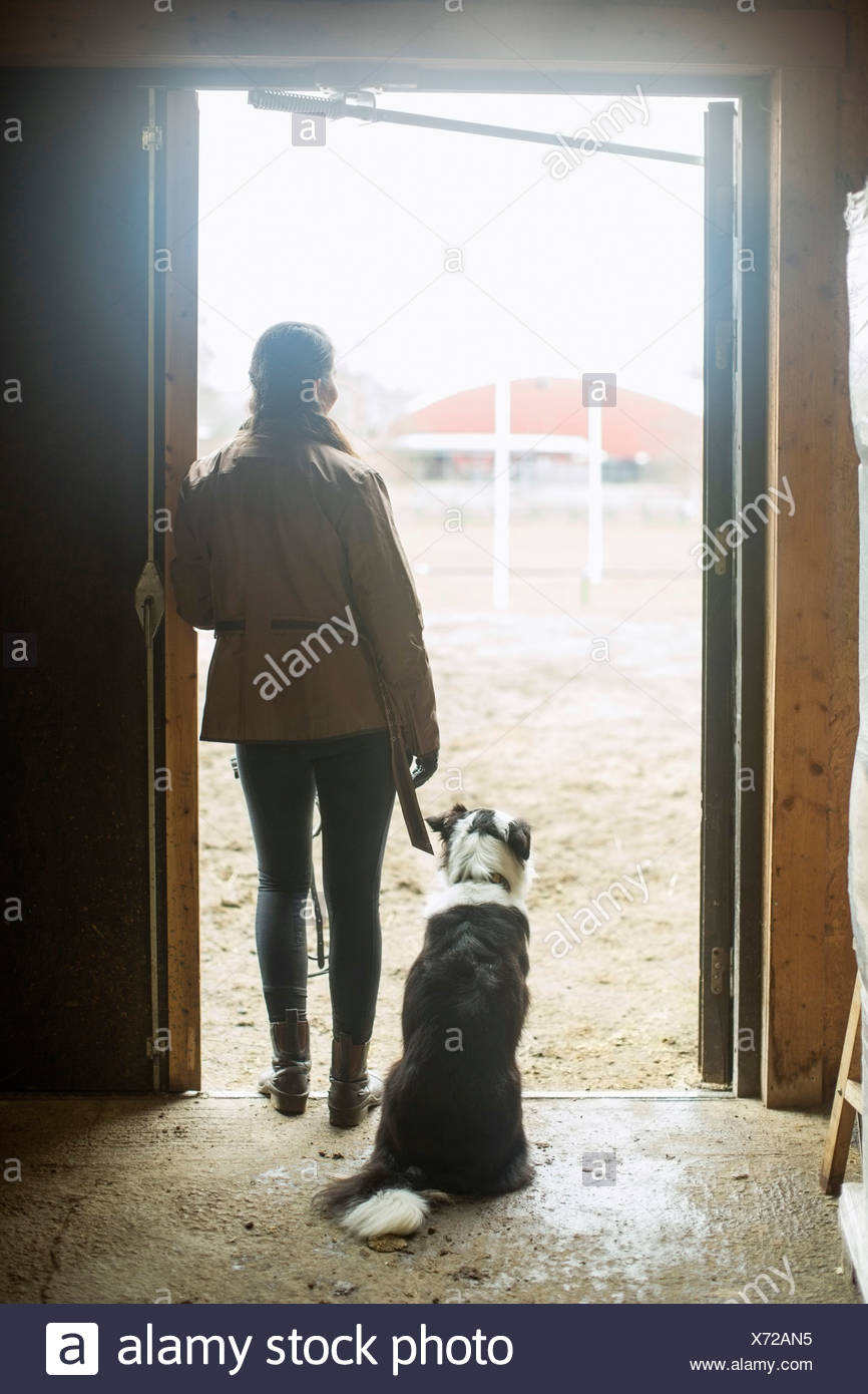 Full length rear view of young woman with dog leaning in doorway of horse stable - Stock Image