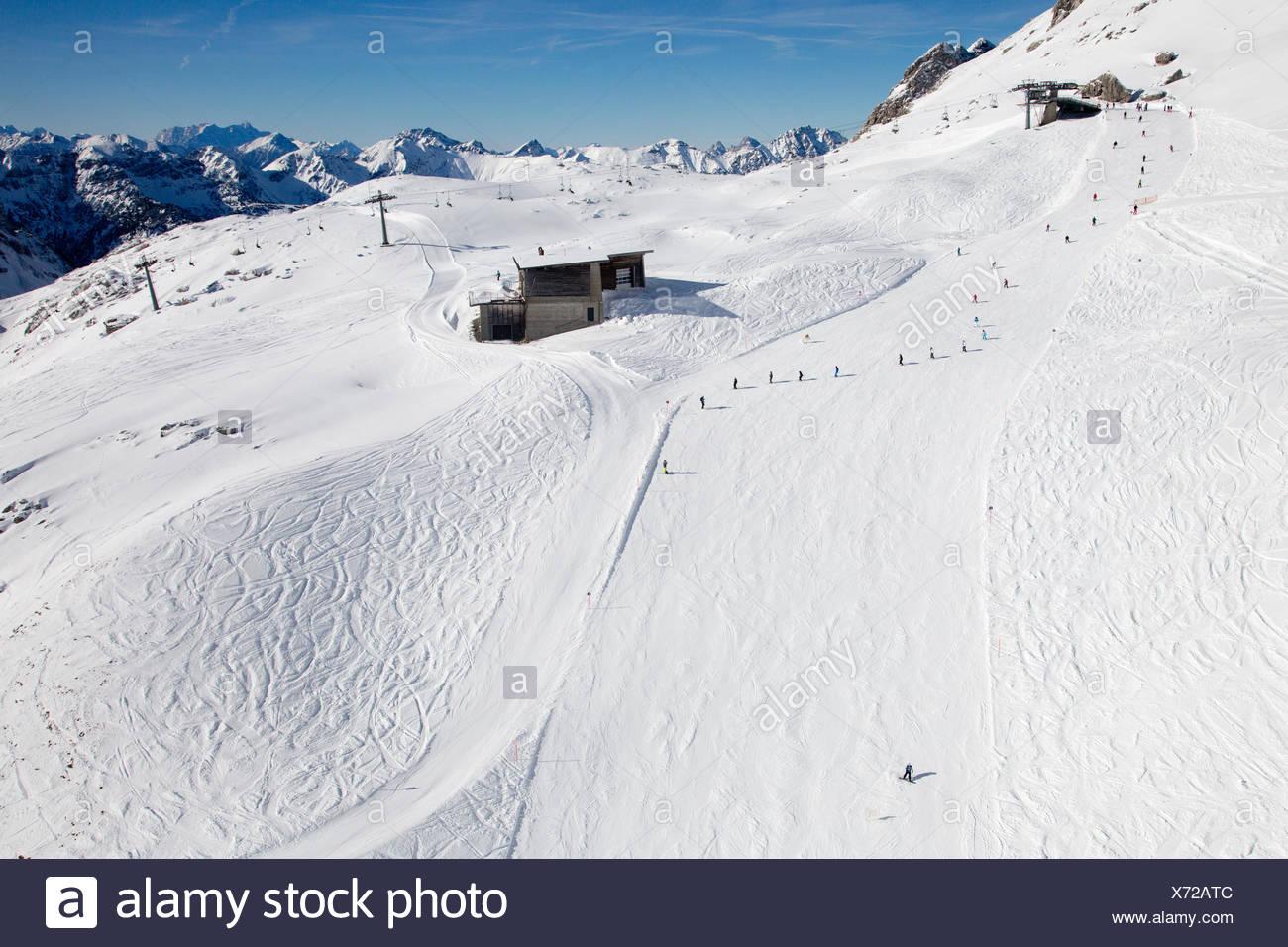 Mit Schnee bedeckte Skipiste mit Skifahrern und Snowboardern in den Bergen Alpen Stock Photo