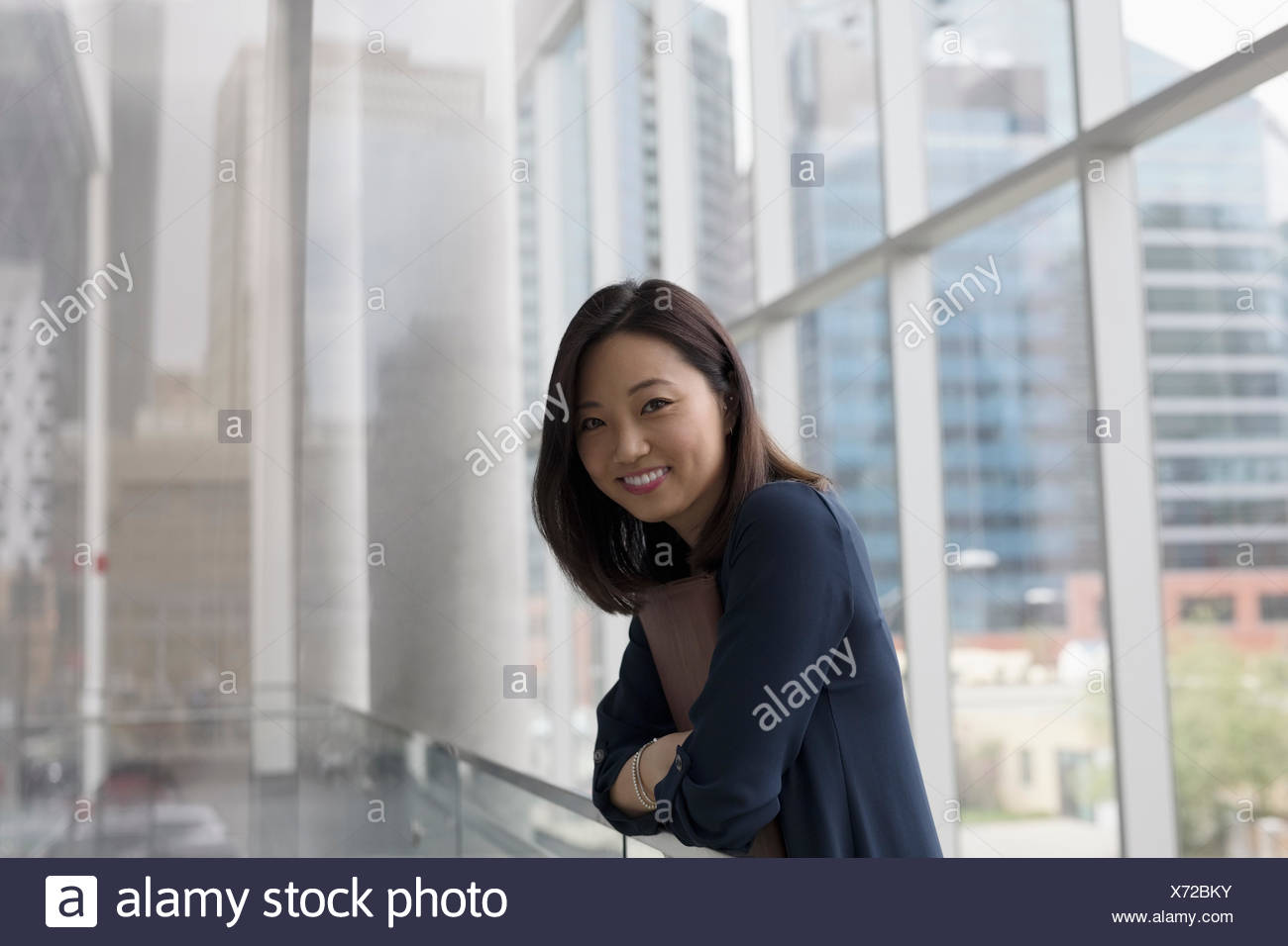 Portrait smiling businesswoman in highrise office corridor - Stock Image