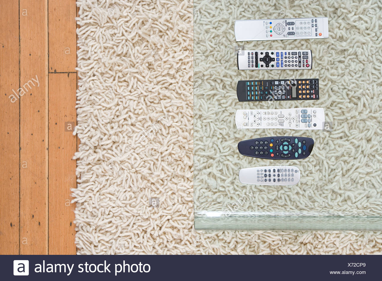 Remote controls on coffee table - Stock Image