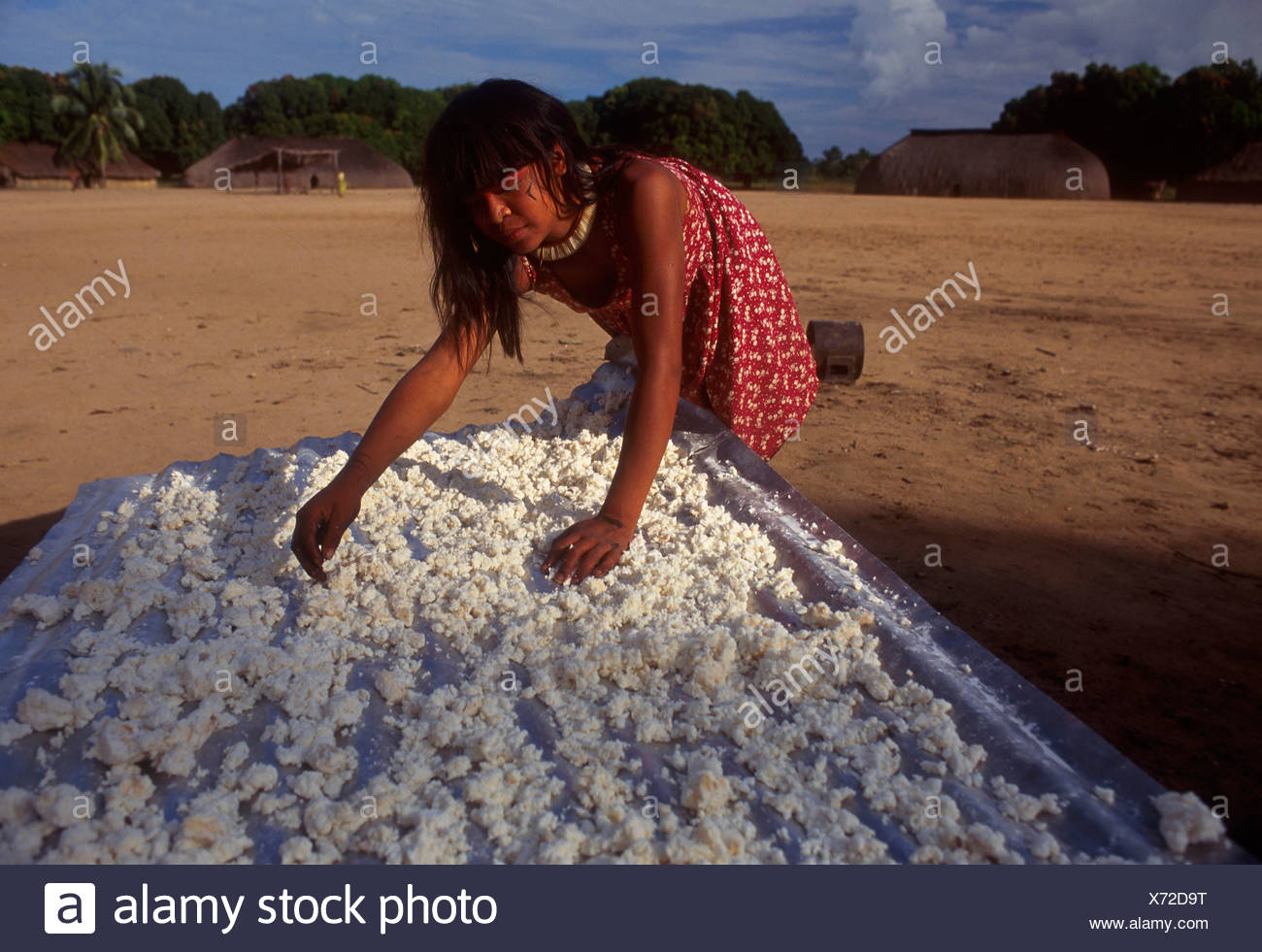 Mehinako Indigenous People Xingu Amazon rain forest Brazil Manioc flour Indigenous women wearing dress - Stock Image