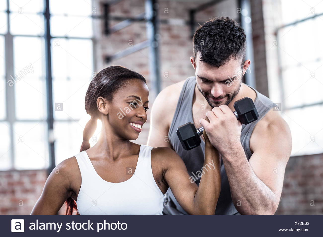 Personal trainer working with client holding dumbbell Stock Photo