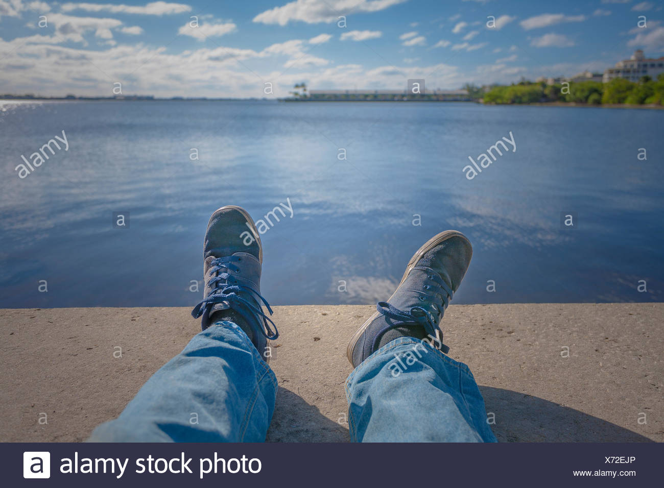 Man's feet and legs near a body of water. - Stock Image