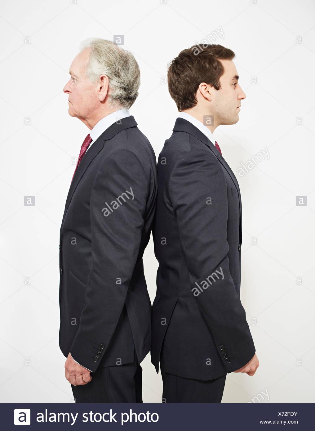 Businessmen standing back to back - Stock Image