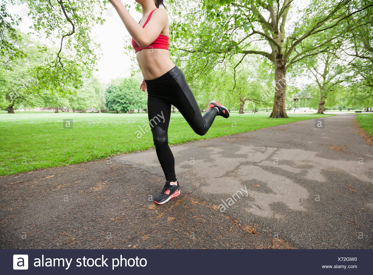 Low section of young woman jogging in park - Stock Image