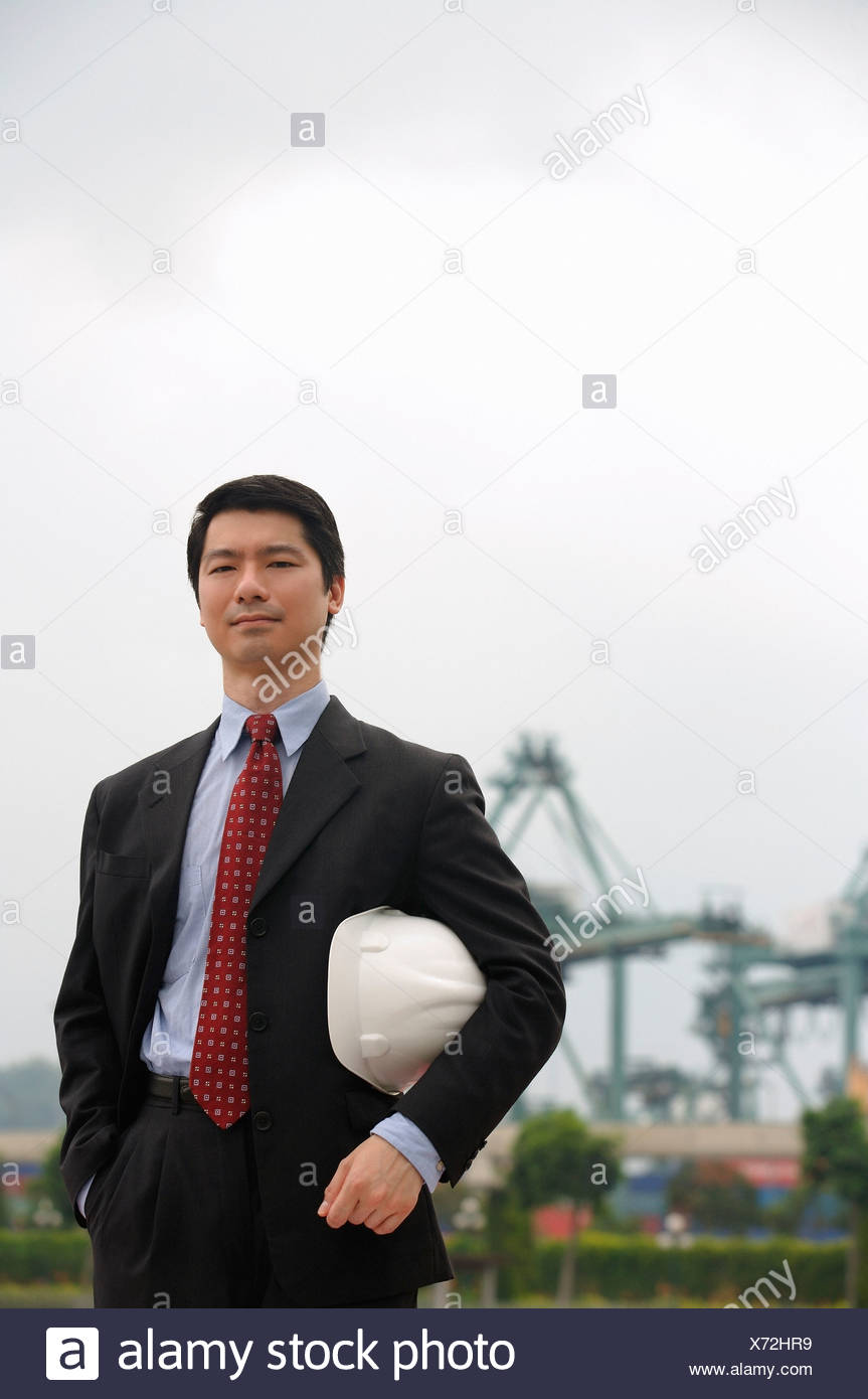 Man with hard helmet looking at camera - Stock Image