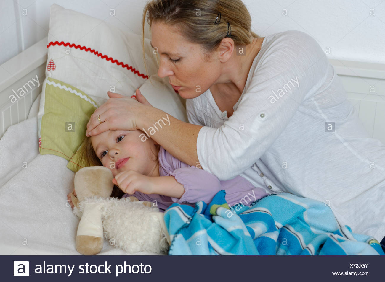 Mother taking care of her sick daughter, child lying in bed - Stock Image