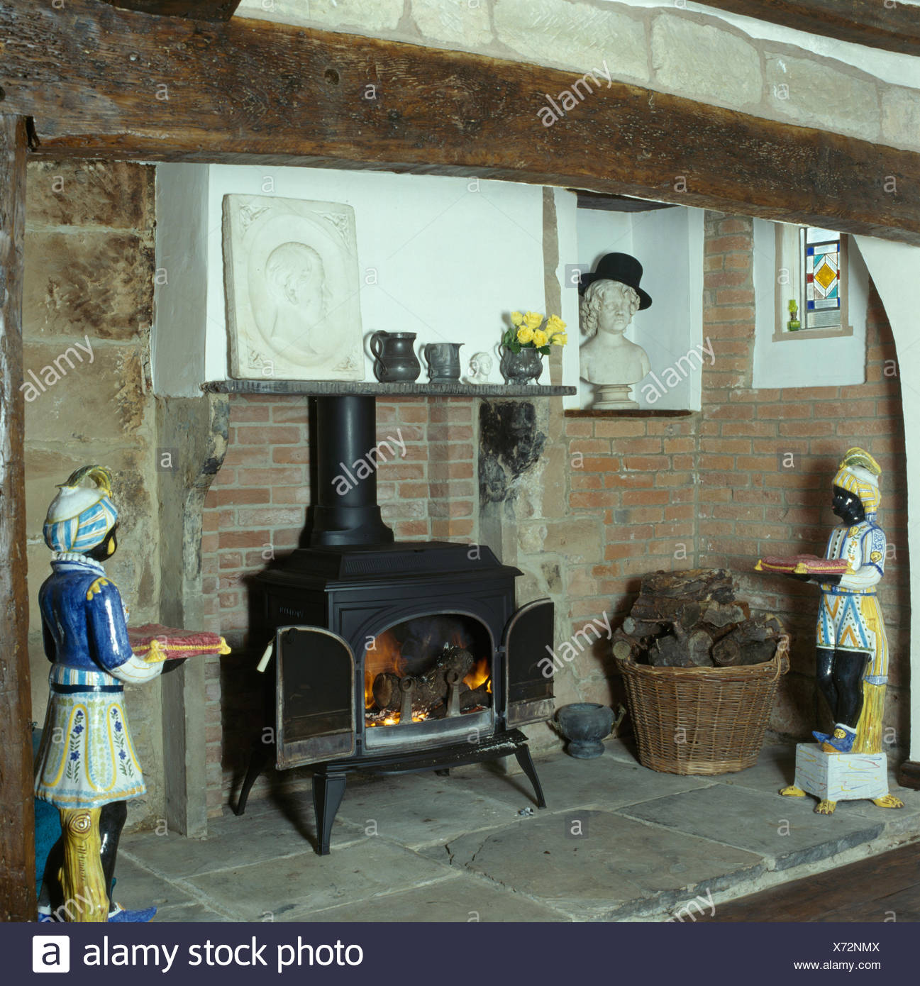 Blackamoor china figures either side of a wood burning stove in an inglenook fireplace Stock Photo