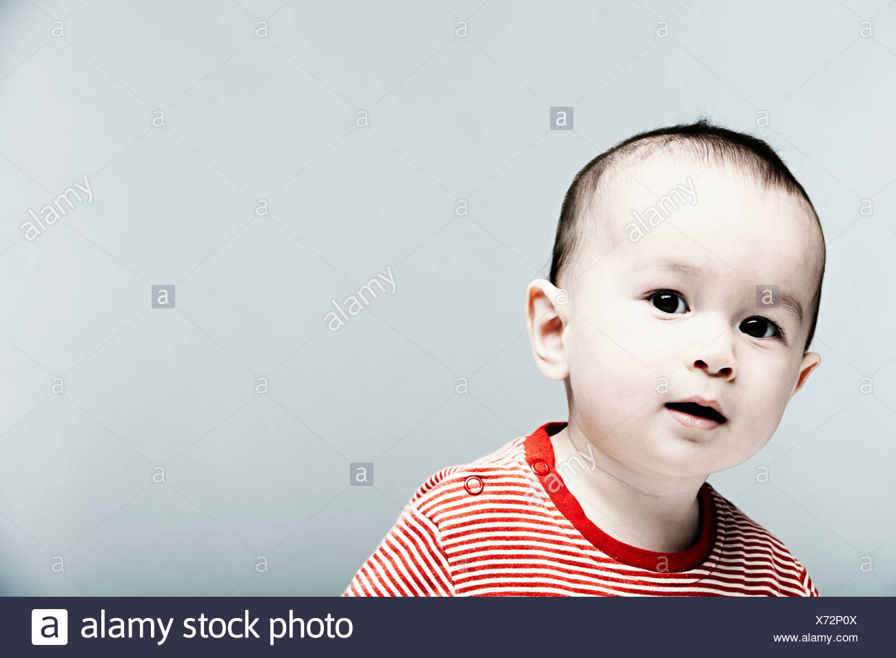 Portrait of baby boy wearing striped top looking at camera - Stock Image