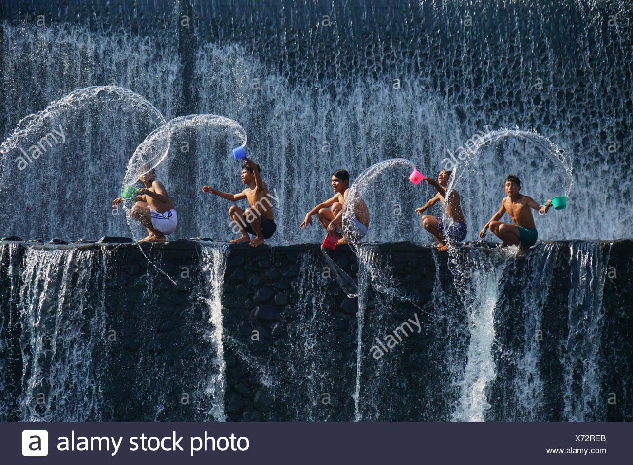 Five children splashing water, Tukad Unda Dam, Bali, Indonesia - Stock Image