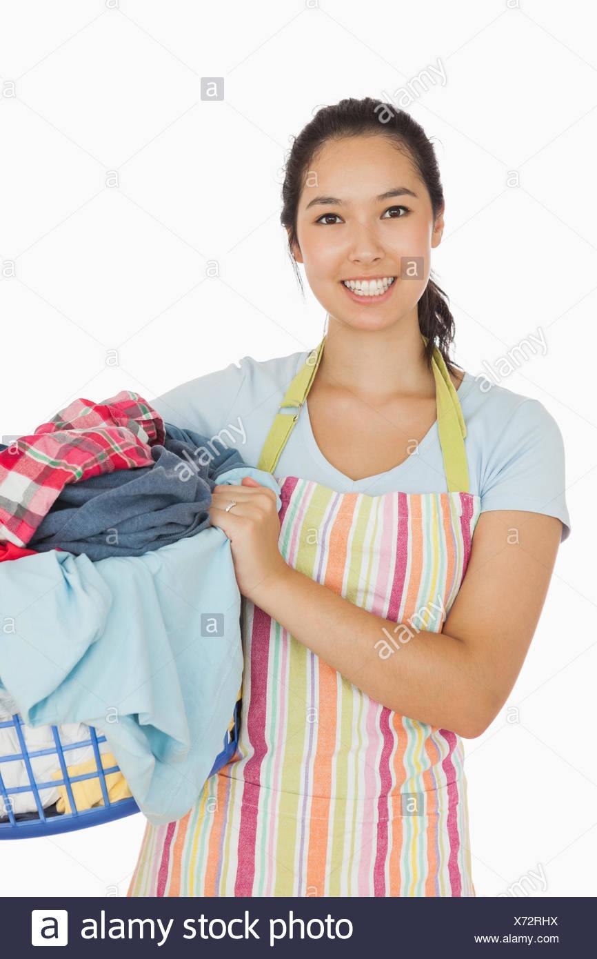 Smiling woman holding laundry basket - Stock Image