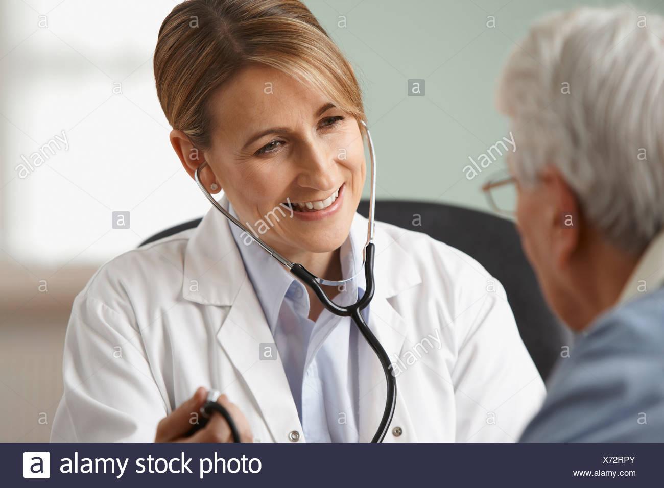 Doctor taking senior mans blood pressure, close up - Stock Image