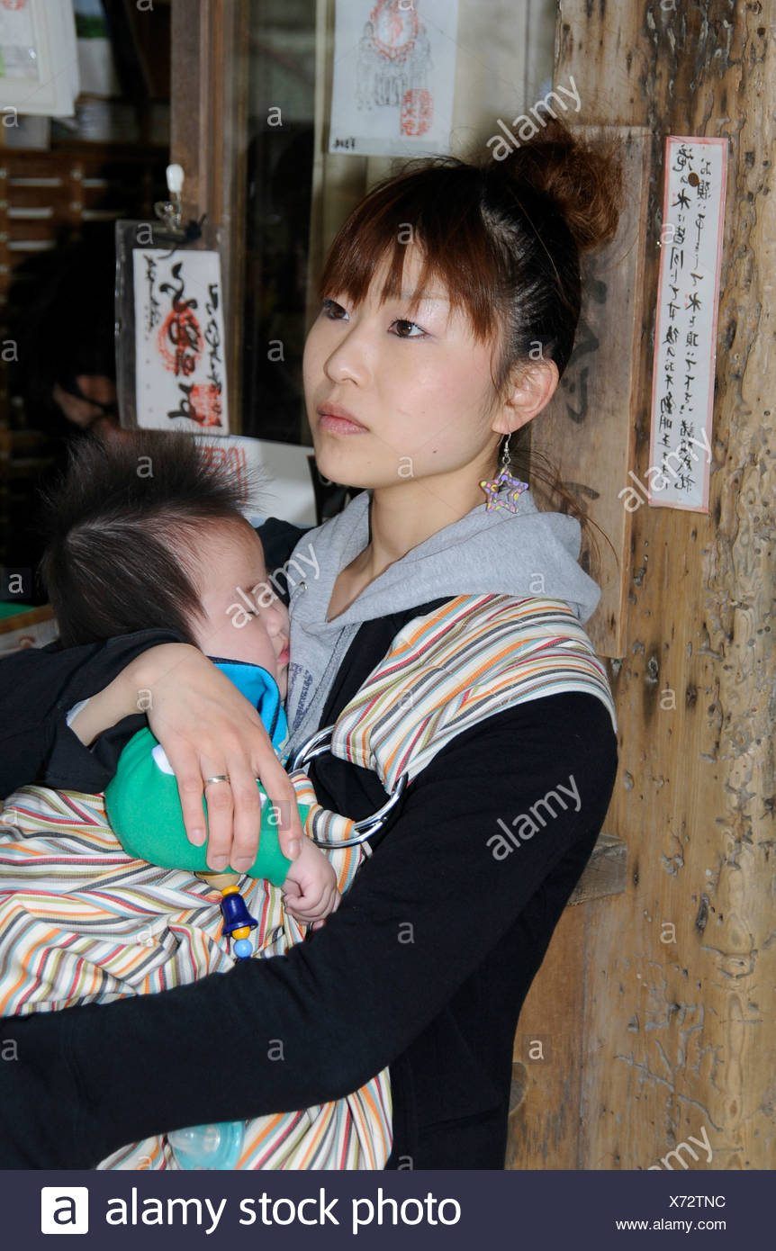Young Japanese woman holding a baby, Kyoto, Japan, Asia - Stock Image