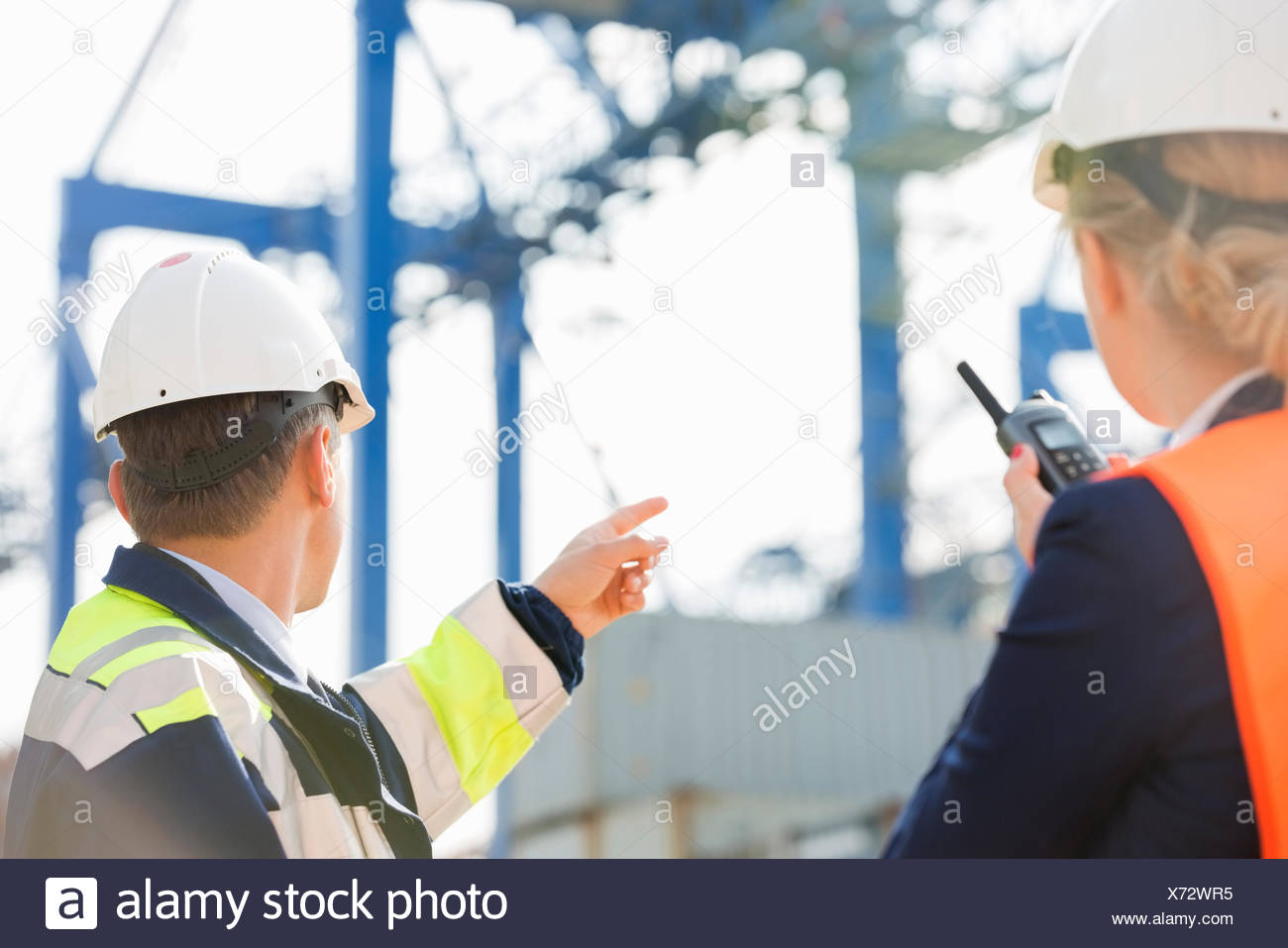 Male and female workers working in shipping yard - Stock Image