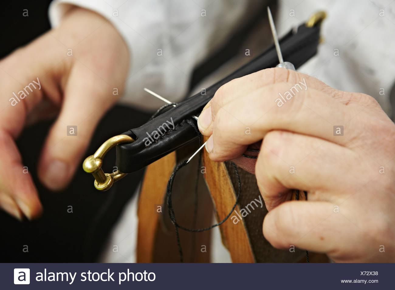 Close up of hands stitching leather - Stock Image