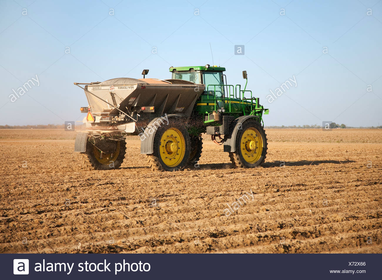 A John Deere 4920 with a New Leader spreader applies dry fertilizer containing Phosphorus and Potassium to a bedded field. - Stock Image