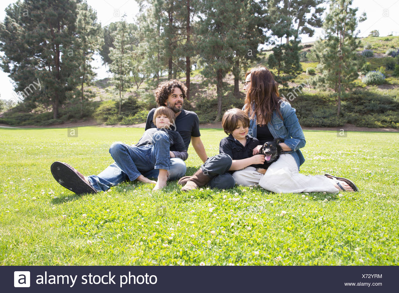 Family with two boys and dog sitting in park Stock Photo